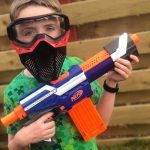 boy holding nerf gun with goggles