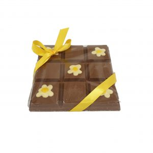 chunky milk chocolate slab with fried egg decoration and yellow ribbon cocoabean