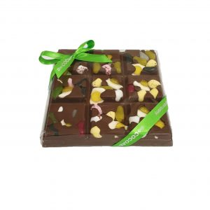 chunky milk chocolate slab with easter themed sweets and green ribbon cocoabean