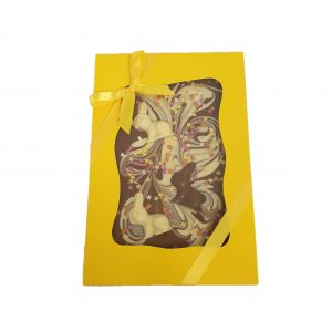 large milk chocolate easter themed slab in yellow box with yellow ribbon