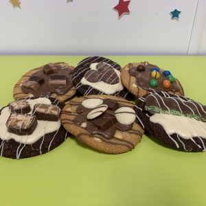 siz decorated cookies on green table