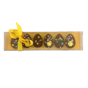 small half egg chocolates with easter spring decoration in a yellow box with yellow ribbon