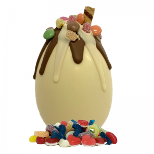 white chocolate easter egg with dripping chocolate and mixed sweets